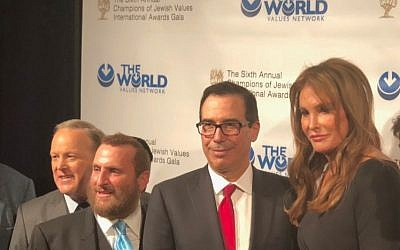 Former Olympic gold medalist Caitlyn Jenner (R) is honored as a 'great friend' to Israel at the annual World Values Network dinner, March 8, 2018. Also pictured, from left: Sean Spicer, Rabbi Shmuley Boteach, Steve Mnuchin. (Danielle Ziri/Times of Israel)