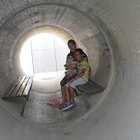 Illustrative: An Israeli family takes cover in a bomb shelter made of a converted concrete pipe during the 2014 Gaza war. (Melanie Lidman/Times of Israel)