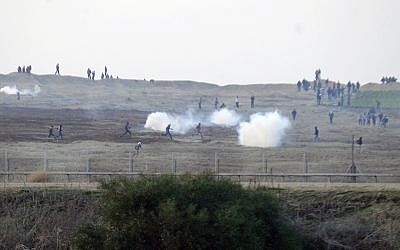 Illustrative photo of Palestinian demonstrators near the Israeli border fence with the Gaza Strip as the IDF shoots tear gas at them, January 3, 2014. (David Buimovitch/Flash90)