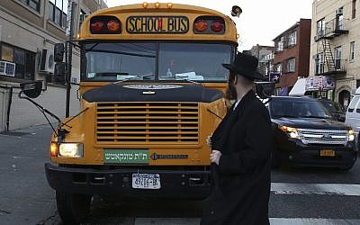 Illustrative: An ultra-Orthodox Jew walks by a Jewish school bus, which has a Yiddish sign on the front, in the Brooklyn neighborhood of Borough Park on January 1, 2014. (Nati Shohat/Flash90)