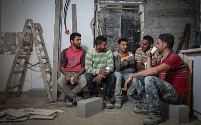 Palestinian construction workers from the West Bank village of Abadiya, during their coffee break at a house under renovation in the Jewish settlement of Alon, south of Jerusalem, on February 16, 2016. (Hadas Parush/Flash90)