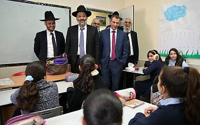 Tiberias mayor Yossi Ben-David (right, without hat), with Interior Minister  Aryeh Deri (center) during a visit to schools in the northern Israeli city of Tiberias, December 20, 2016. (Yaacov Cohen/Flash90)