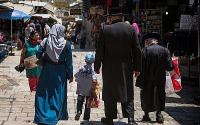 A Palestinian Muslim woman walks by ultra-Orthodox Jewish men in the Muslim Quarter of Jerusalem's Old City, on June 18, 2017. (Hadas Parush/Flash90)