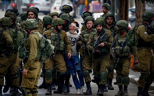 16-year-old Fawzi al-Junaidi (c) is arrested by Israeli soldiers at a protest in Hebron, December 7, 2017. (Wisam Hashlamoun/Flash90)