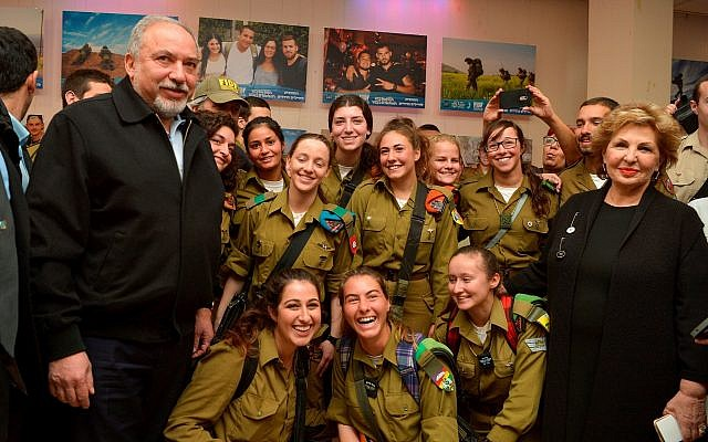 Defense Minister Avigdor Liberman (L) and Immigration Absorption Minister Sofa Landver (R) pose for a picture with lone soldiers at an event in Tel Aviv on January 25, 2018. (Flash90)