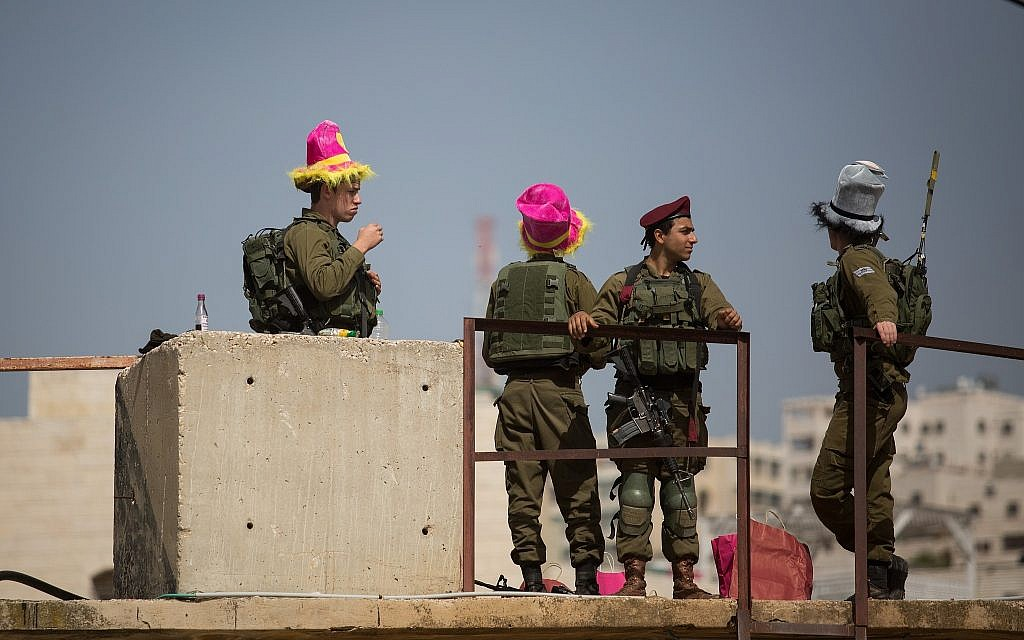 Israeli soldiers stand guard during the annual parade marking the Jewish holiday of Purim in the West Bank city of Hebron on March 1, 2018. (Hadas Parush/Flash90)