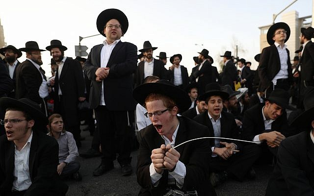 Ultra orthodox Jewish men protest against the army draft, at the entrance to Jerusalem on March 8, 2018. (Yonatan Sindel/Flash90)