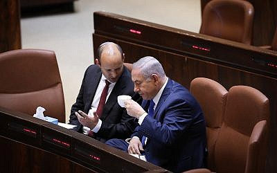 Prime Minister Benjamin Netanyahu speaks with Education Minister Naftali Bennett (L) at the Knesset on March 12, 2018. (Miriam Alster/Flash90)