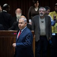 Prime Minister Benjamin Netanyahu is seen running to place his vote, at the Knesset on March 13, 2018. (Hadas Parush/Flash90)