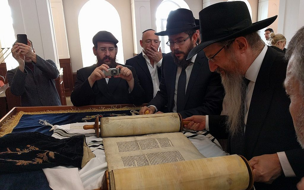 From right: Russian chief rabbi Berel Lazar, rabbi Levi Kaminetsky, and Baruch Ramatsky examine the Torah scroll Ramatsky's family has kept for the last 90 years, in the main synagogue of Tomsk, February 1, 2018. (Yaakov Schwartz/Times of Israel)