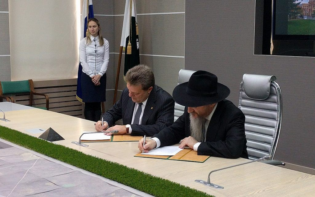 Mayor of Tomsk Ivan Klyayn, left, and Russian chief rabbi Berel Lazar sign agreement returning the Cantonist synagogue to the Jewish community at Tomsk City Hall, February 1, 2018. (Yaakov Schwartz/Times of Israel)