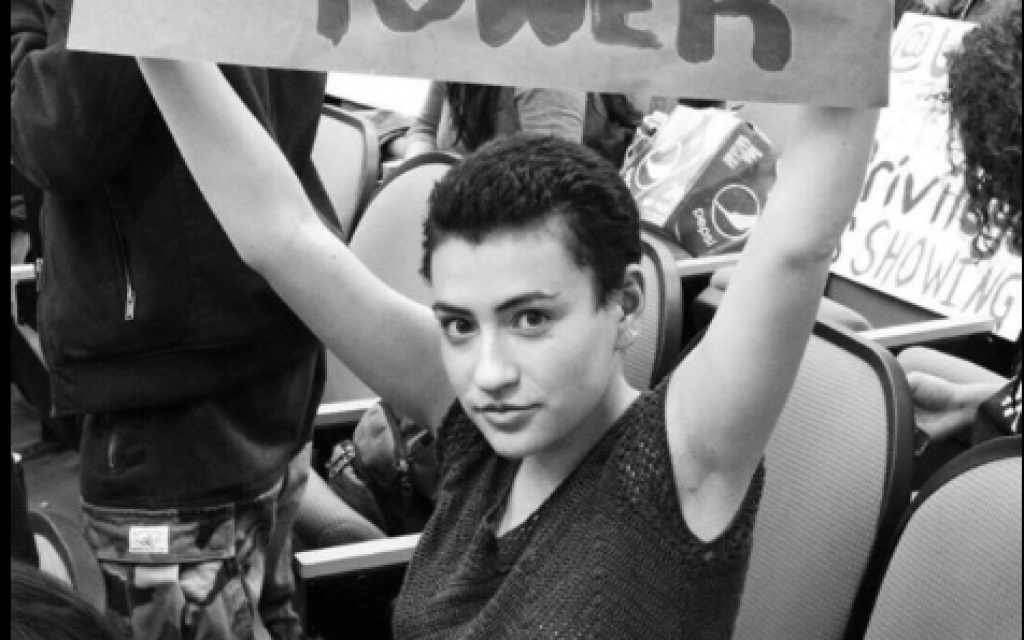 Nesha Ruther, co-president of Students for Justice in Palestine at the University of Wisconsin-Madison campus, holding up a sign supporting marginalized groups. (Courtesy)