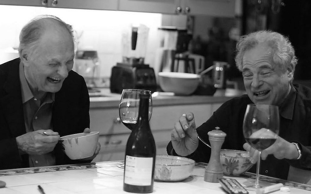 Itzhak Perlman, right, having dinner with Alan Alda from a scene in 'Itzhak.' (Courtesy of Greenwich Entertainment/via JTA)