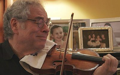 Itzhak Perlman, shown in a scene from the documentary 'Itzhak,' has endured hardships to become perhaps the most famous violinist in the world. (Courtesy of Greenwich Entertainment/via JTA)