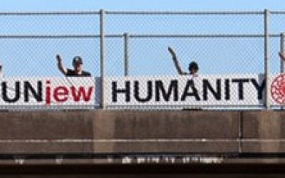 White supremacists hang an anti-Semitic banner on a highway overpass that reads 'UnJew Humanity' (Courtesy: Anti-Defamation League)