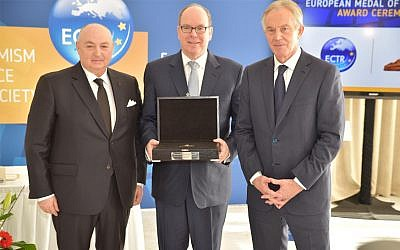 Prince Albert II of Monaco, center, receiving a medal from ECTR President Moshe Kantor, left, and ECTR chair, Tony Blair, on March 6, 2018 in Monte Carlo. Photo: (Courtesy of ECTR via JTA)