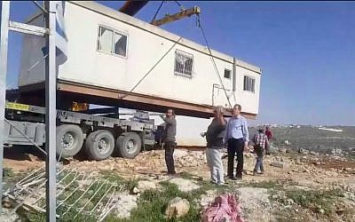 A crane places a caravan on the hilltop of a new industrial zone in the West Bank settlement of Kiryat Arba on March 6, 2018. (Screen capture/Facebook)
