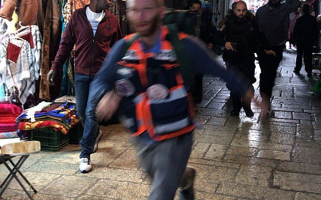 A Medic rushes tend to an Israeli victim of a stabbing attack in the Old City of Jerusalem on March 18, 2018. (Ir Amim)