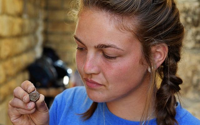 A student from Armstrong College holds a coin discovered at the Ophel archaeological dig outside the walls of Jerusalem's Old City, where a hoard of rare bronze coins from the Jewish Revolt was recently discovered, dating to circa 66-70CE. (Eilat Mazar)