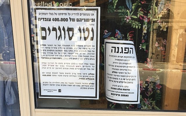 Posters in a shop wiindow on Eilat Street in Tel Aviv's garment district, March 7, 2018 (Simona Weinglass/Times of Israel)