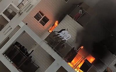 An eight-year-old girl leaps from a blaze on the eighth floor to safety on the sixth floor of a Beersheba apartment block on March 25, 2018. (Screen capture: Ynet news)