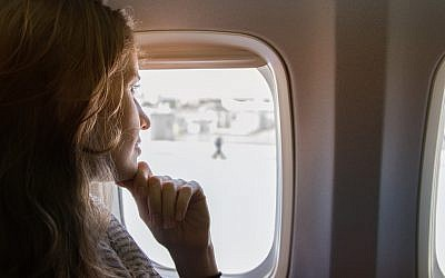 Woman passenger on a plane looking out of the window (via iStock)