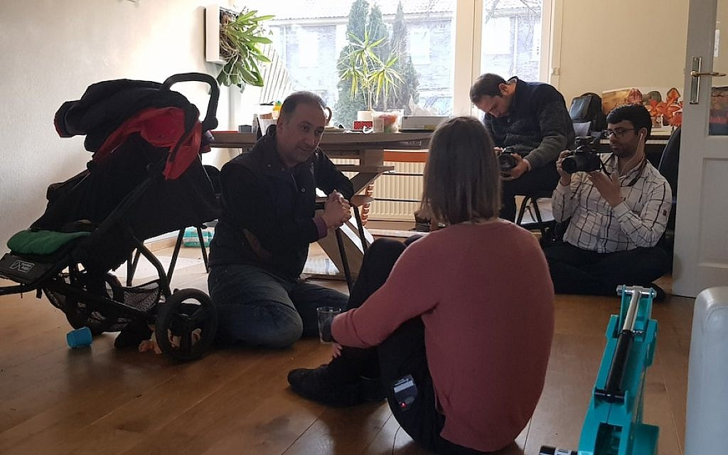 Mohammad Delavari, left, and two members of his filming crew interviewing Iris Tzur at her home in Amsterdam, March 1, 2018. (Cnaan Liphshiz)