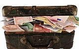 Illustrative image of a suitcase full of cash (ungorf; iStock by Getty Images)