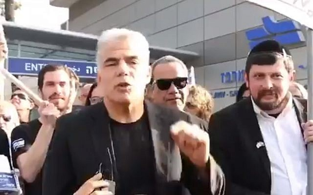 Yesh Atid party leader Yair Lapid (center) protests legislation to exempt ultra-Orthodox yeshiva students from military conscription, next to Dave Mandelshtam, who appeared as an ultra-Orthodox protester but was later revealed to be a Yesh Atid activist who had dressed up, Tel Aviv, March 4, 2018. (Screenshot)
