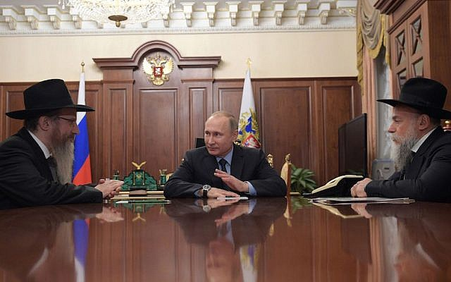 Russian President Vladimir Putin speaks with Russian Chief Rabbi Berel Lazar, left, and Alexander Boroda, head of the Federation of Jewish Communities, during their meeting at the Kremlin in Moscow, December 28, 2016. (Alexei Druzhinin/AFP/Getty Images via JTA)