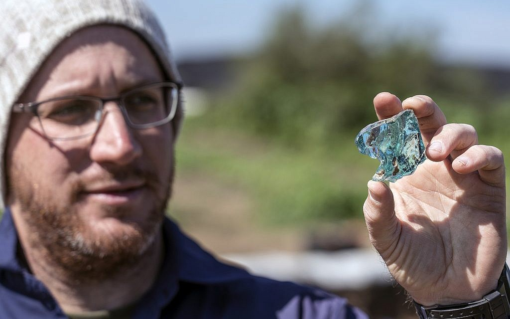 Archaeologist Yair Amitzur holding a chunk of glass discovered during preparations for the new Sanhedrin Trail in the Galilee. According to Amitzur, the find is evidence of the glass industry from the time of the Sanhedrin. (Yaniv Berman, Israel Antiquities Authorit)