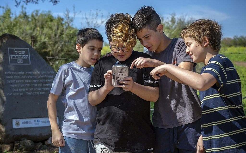 Students examine the Galilee's Sanhedrin Trail web application next to the smart stone positioned along the route. (Yaniv Berman, Israel Antiquities Authority)