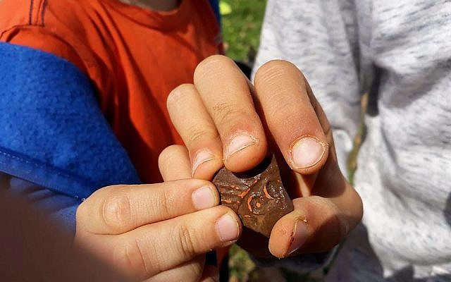 Pupils from Benzion Netanyahu school in the West Bank settlement of Barkan hold a piece of 1,500 pottery that was once part of an oil lamp. (courtesy)