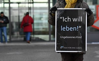 A woman holds a placard as she protests against childbearing abortions in front of the entrance of a local health authority in the Freiham district of Munich, southern Germany, on March 20, 2018. (AFP PHOTO / CHRISTOF STACHE)