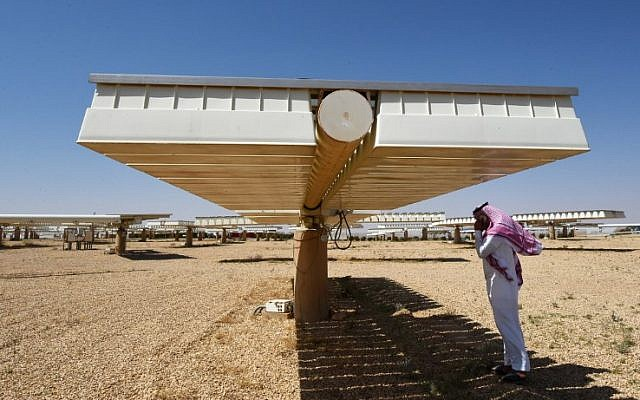 A Saudi man talks on his mobile under the shade of solar panel at a solar plant in Uyayna, north of Riyadh, on March 29, 2018. (FAYEZ NURELDINE/AFP)