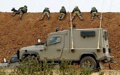 Illustrative: Israeli soldiers take aim, as they lie on an earth barrier along the border with the Gaza Strip, near the southern Israeli kibbutz of Nahal Oz, on March 30, 2018. (Jack Guez/AFP)