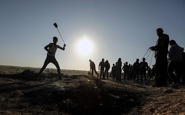 A Palestinian protester hurls stones toward Israeli soldiers during a demonstration along the border with Israel, east of Gaza City on March 31, 2018. (AFP PHOTO / MAHMUD HAMS)