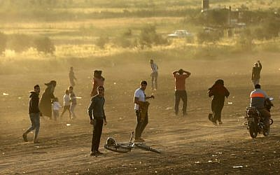 Palestinian protesters run for cover from tear gas fired by Israeli security forces during a protest along the border with Israel, east of Gaza City in the Gaza Strip on March 31, 2018. (AFP PHOTO / MAHMUD HAMS)