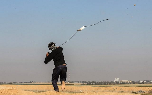 A Palestinian man swings a slingshot during clashes with Israeli security forces near the border with Israel, east of Khan Younis, in the southern Gaza Strip, on April 1, 2018. (AFP/ SAID KHATIB)