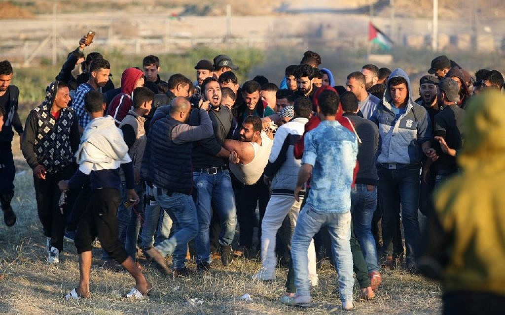 Palestinian protesters carry an injured comrade during clashes with Israeli forces following a protest along the border with Israel, east of Gaza City on April 1, 2018.(AFP PHOTO / Mohammed ABED)