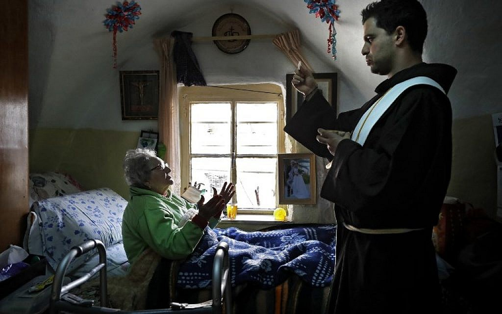 Franciscan friar Ayman Bathesh (R) gives communion to an elderly ill Christian woman at her home in the Old City of Jerusalem, on February 12, 2018. (AFP PHOTO / Thomas COEX)