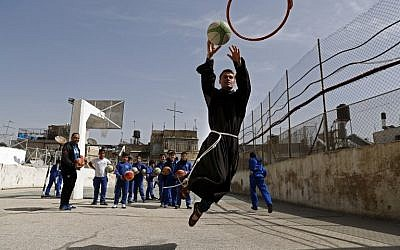 A Franciscan friar plays basketball with children from the Terra Sancta school during a sport session in the Old City of Jerusalem, on March 1, 2018. (AFP PHOTO / Thomas COEX)