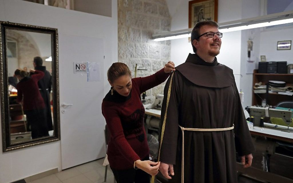 A Palestinian Christian tailor measures a Franciscan friar for a new penitent robe at a sewing workshop inside the Saint Saviour Convent, the Franciscan headquarters in the Old City of Jerusalem, on February 2, 2018. (AFP PHOTO / Thomas COEX)