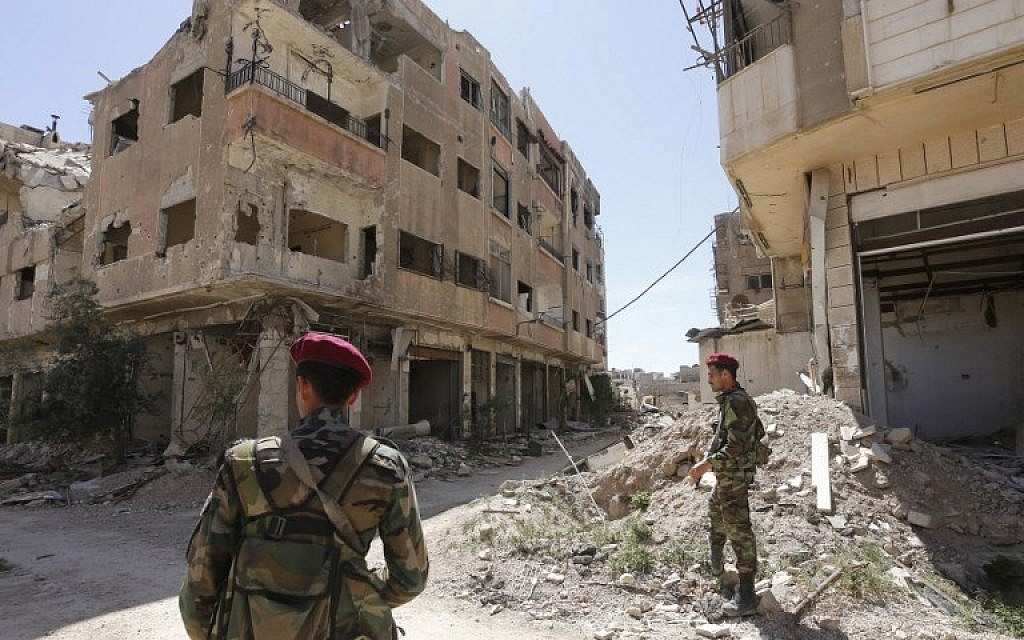 Regime forces walk along a destroyed street in the former rebel-held town of Jobar in Eastern Ghouta on April 2, 2018. (AFP PHOTO / Louai Beshara)