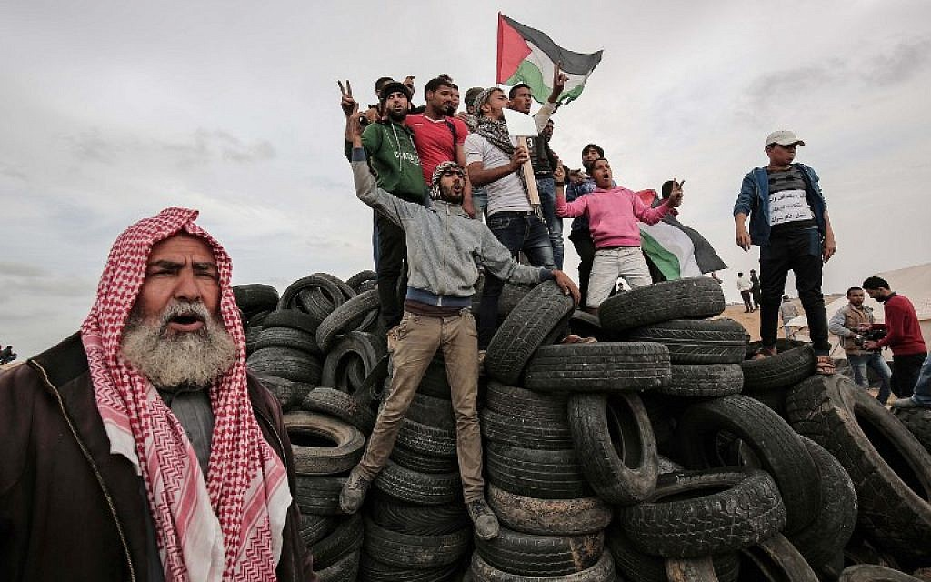 Palestinian protesters wave their national flag on a tire pile near the border with Israel, east of Khan Yunis, in the southern Gaza Strip, on April 3, 2018, ( AFP PHOTO / SAID KHATIB)