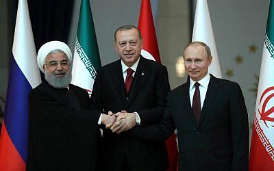 Turkish President Recep Tayyip Erdogan (C), Russian President Vladimir Putin (R) and President of Iran, Hassan Rouhani (L) pose for a photo ahead of the Turkey-Russia-Iran Tripartite summit in Ankara, Turkey on April 04, 2018.  (AFP PHOTO / POOL / TOLGA BOZOGLU)