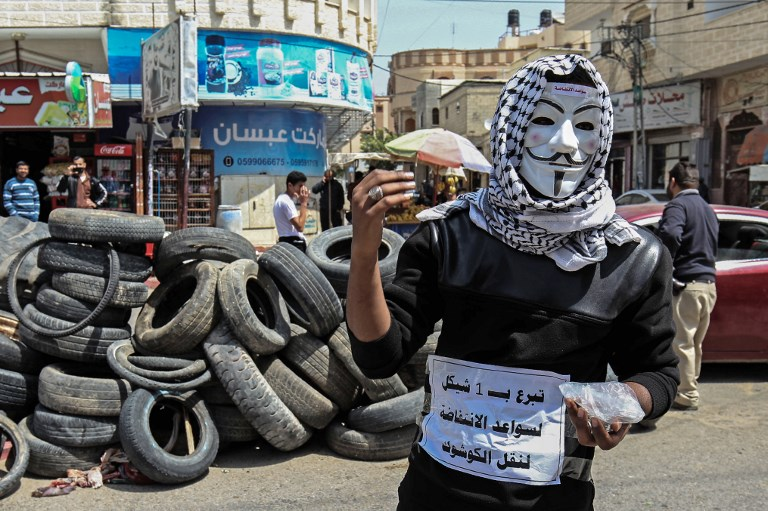 A Palestinian youth collects money and tires in Khan Younis in the southern Gaza Strip
