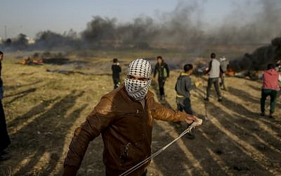 A Palestinian protestor uses a slingshot to throw a stone during clashes with Israeli forces following a tent city gathering at the Israel-Gaza border east of Gaza City on April 4, 2018. (AFP  MAHMUD HAMS)