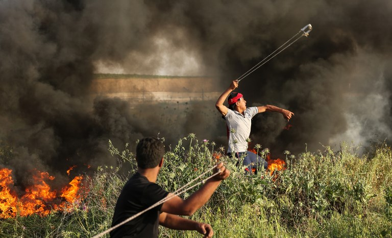 Palestinian protesters use slingshots to throw stones during clashes with Israeli forces at the Israel Gaza border east of Gaza City