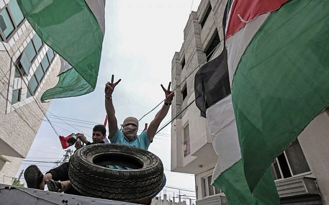 Palestinian men sit in a trailer loaded with tires to be used in protests in Rafah, in the southern Gaza Strip, on April 5, 2018. (AFP /SAID KHATIB)